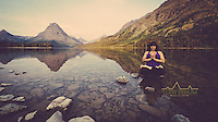 yoga lotus pose on rock in magical mountain lake glacier national park