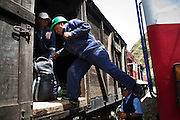 Train workers load the cargo car at Acoria Station. The train was overhauled recently and one of the improvements was forbidding large packages in the passenger cars. They must now go in the designated cargo car.