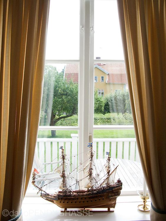 A model ship sits in a window in Sweden.