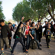 A group of Afghan teenagers celebrating minutes after their boat landed on the beach of Skala Sykaminias. Everyday hundreds of refugees, mainly from Syria and Afghanistan, are crossing in small overcrowded inflatable boats the 6 mile channel from the Turkish coast to the island of Lesbos in Greece. Many spend their life savings, over $1000, to buy a space on those boats.