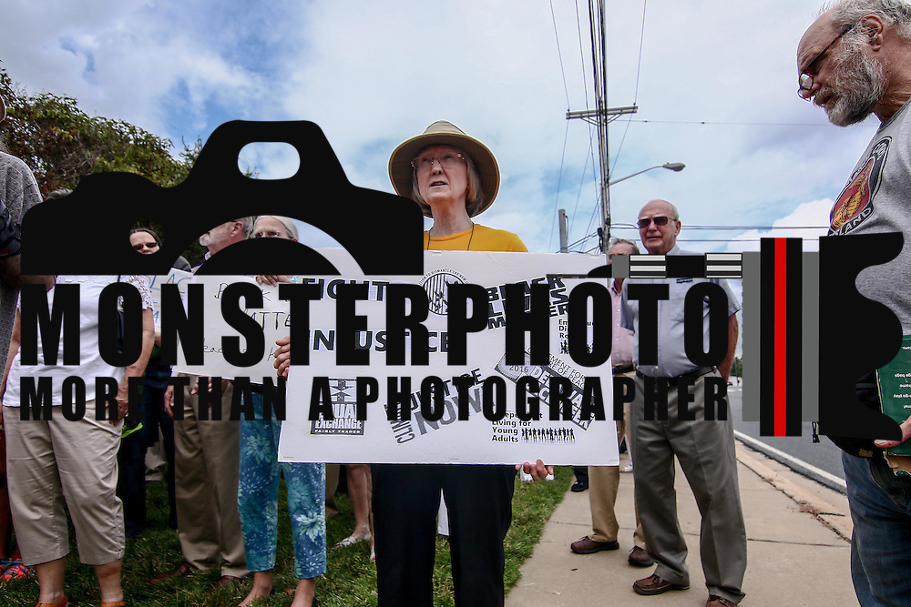 "A members of the First Unitarian Church congregation holds signs that reads ""Fight Injustice"" during a rededication ceremony Sunday, August 21, 2016, at First Unitarian Church in Wilmington."