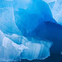 Norway, Svalbard, Spitsbergen, Deep blue iceberg floating near face of Lilliehøøk Glacier in Lilliehøøkfjorden in Krossfjorden on summer morning