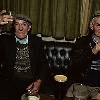 Ireland, County Galway, Lettermore, Corman Hernon raises pint of Guinness Stout with friend in rural pub