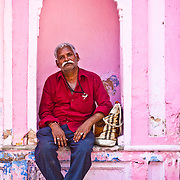 A man sits in a small alcove in the side of a building in Haridwar, India.