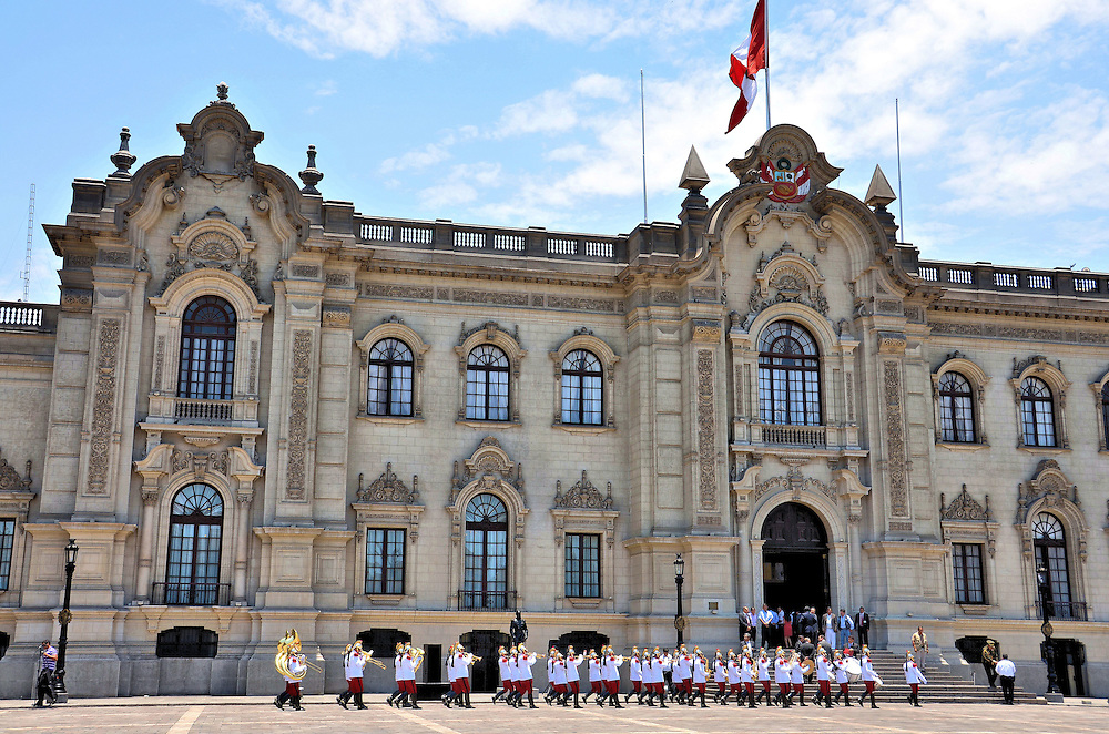 Changing of the Guard at Government Palace in Lima, Peru<br /> Stand in Plaza Mayor in Lima and you are at the 1535 birthplace of this capital city. On each corner is a reflection of Peruvian history including a cathedral and four palaces.  One of them is the Government Palace. Palacio de Gobierno houses the executive branch and the president&rsquo;s residence. Dragoon Guards protect this French Baroque building inside and outside the wrought-iron fence. The changing of the guard ceremony, accompanied by a band, occurs daily at noon.