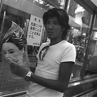 Man carrying the head of a mannequin, in a bag, in Shibuya, Tokyo, Japan.