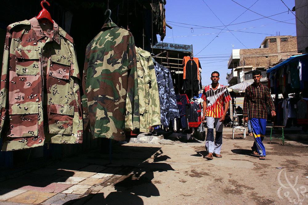 "Iraqi men walk past a shop selling military uniforms of the Army and Special Police commandos in the notorious ""Thieves Market"" April 27, 2006 in the Bab al-Sharji district of Baghdad, Iraq. More than a dozen stores in the market openly sell the counterfeit uniforms, which officials say are regularly used by insurgents to commit crimes or engage in sectarian violence."