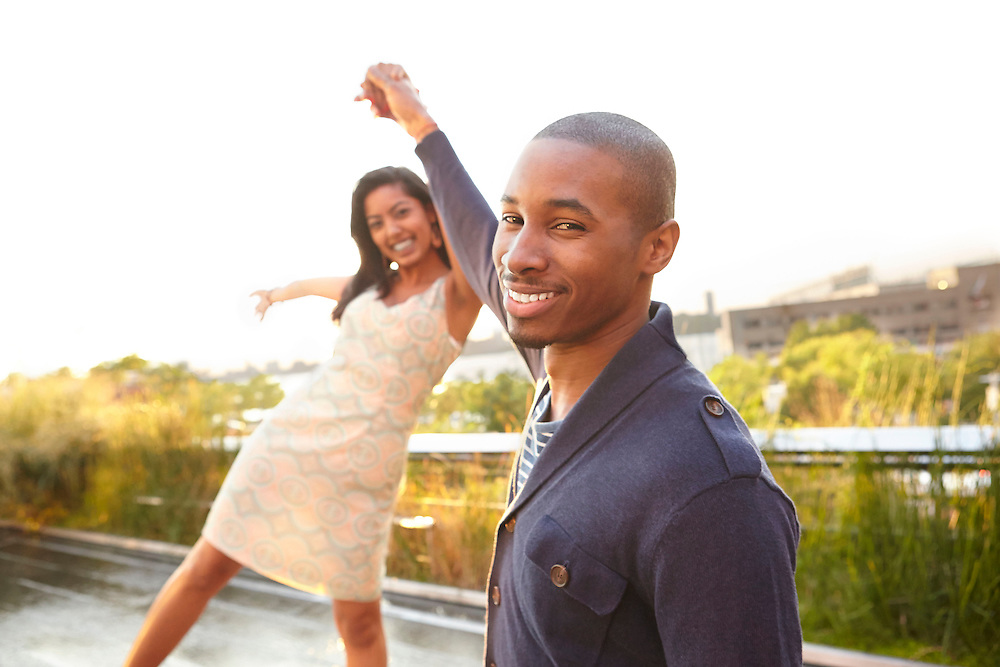 Lifestyle image of Indian and African American couple dancing outside in New York City