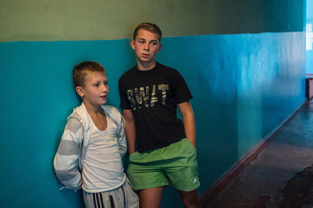 DNIPRODZERZHINSK, UKRAINE - OCTOBER 11: Oleg (L) and Yegor stand in a hallway at the sports school where they live with about 60 other displaced people from Eastern Ukraine on October 11, 2014 in Dniprodzerzhinsk, Ukraine. The United Nations has registered more than 360,000 people who have been forced to leave their homes due to fighting in the East, though the true number is believed to be much higher.(Photo by Brendan Hoffman/Getty Images) *** Local Caption ***
