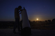 A man looking at the sky through a telescope  with the full moon rising on the horizon, near Reguengos de Monsaraz , in the Alentejo region, in Portugal.