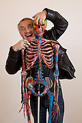 "Damien Hirst Portrait with his artwork.""St Elmo's Fire"".2008.Household gloss on plastic skeleton.1700 x 425 x 435 mm.© Damien Hirst. All rights reserved, DACS 2010.Photographed in his Chalford Studio, near Stroud, Gloucestershire"