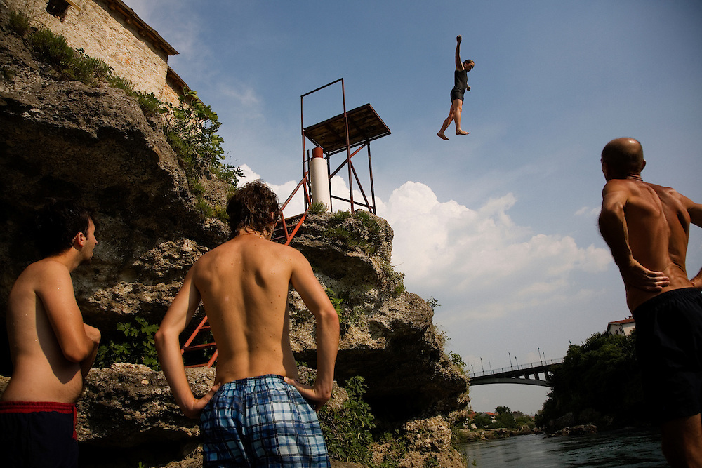 """Øyvind, a 20year old Norwegian tourist, practices his technique from the 10m platform under the watchful eye of veteran Mostari Adem Mocca Pajevic before attempting his jump from the Old Bridge...Divers and tourists at Mostar's famous Old Bridge (Stari Most) in Bosnia and Herzegovina. This bridge is the city and region's biggest tourist attraction and there are busses full of tourists coming in from Sarajevo and Dubrovnik, Croatia. For 25euros tourists can train to jump from the bridge themselves, under supervision from the """"professional"""" Mostar divers known as the Mostari. .."""