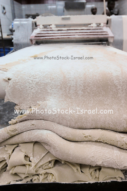 Industrial Bakery. Dough comes out of the rolling machine