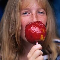 USA, Maryland,Oakland, Sarah Slattery eats candy apple along the parade route of Garrett County Autumn Glory Festival