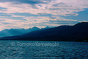 An early morning view at Lake Zurich, Switzerland of silhouetted mountains with clouds slightly tinged with red..The lake water looks choppy with small waves everywhere