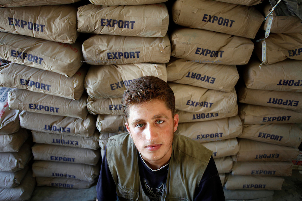 A young man in front of stockpiled cement bags in his shop in Koreen.<br />