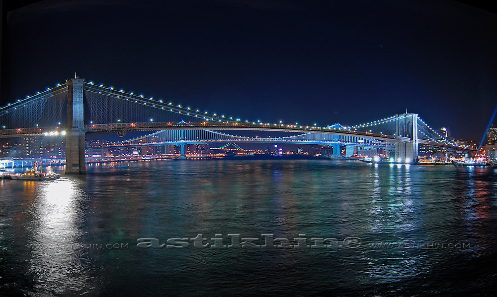 View of Brooklyn, Manhattan and Williamsburg Bridges on East River at night.