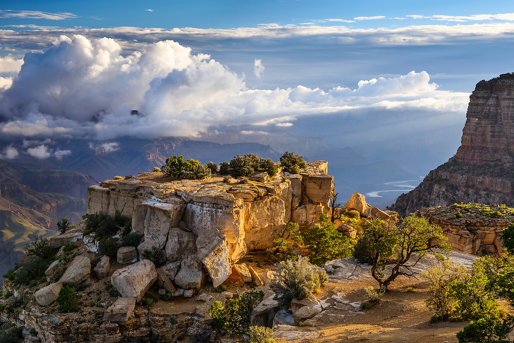 Clouds shroud the North Rim of the Grand Canyon as the first rays of daylight permeate the depths of the canyon including the Colorado River.