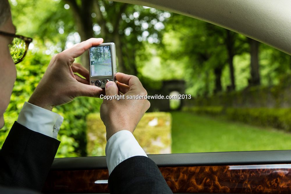 Interior architectThierry THENAERS takes a photograph out of his car, of an old doorway to a garden at next to the Castle of Anthée  in Anthée, Belgium, 10th of June 2013. Credit Sander de Wilde for The Wall Street Journal.  Castle