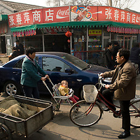 Traffic jam in a Beijing hutong involving different means of transport.