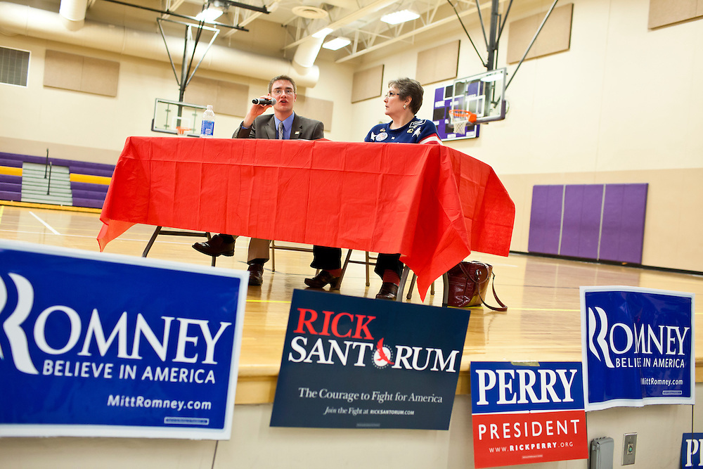 Voting results are announced at a caucus site at Summit Middle School on Tuesday, January 3, 2012 in Johnston, IA.