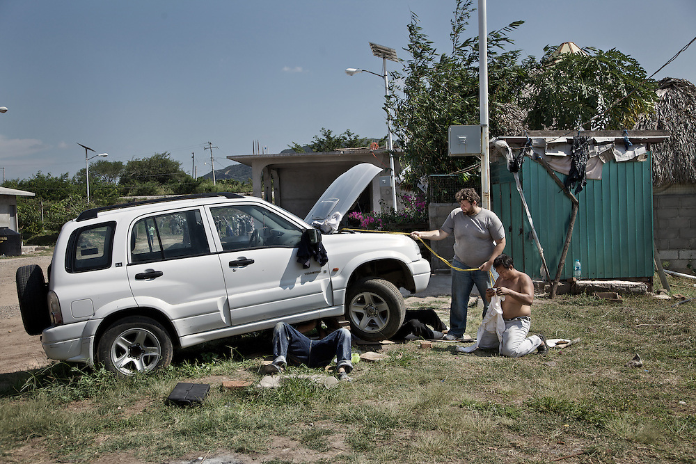 Volunteers of the shelter repairing the only car that allows them to move in case of emergencies. Ixtepec-Oxaca-Mexico,2011