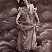 Woman standing on the globe with the moon over her shoulder, circa 1900.french realphoto.fantasy, moon, world, women, vintage