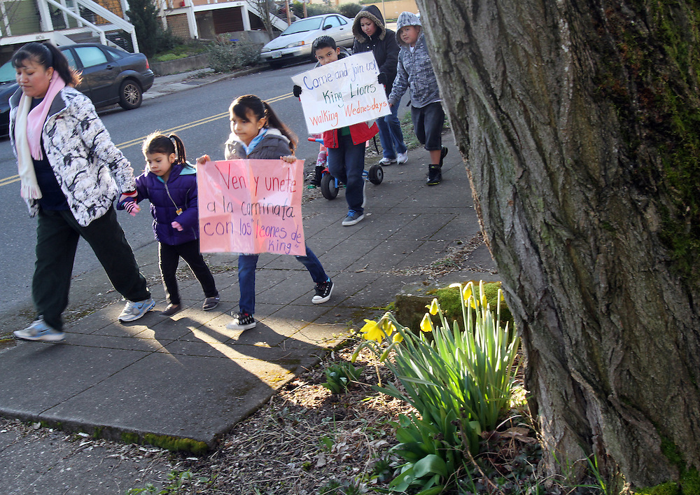 Members of a Latino parent group walk their children to King Elementary School before a weekly parent-teacher meeting on Wednesday, March 7, 2012.