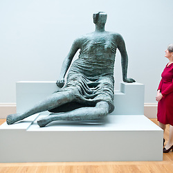 "London, UK - 13 May 2013: Penelope Curtis, director at Tate Britain poses for a picture next to a sculpture by Henry Moore entitled ""Draped Seated Figure 1957-8"". The new chronological presentation of the world's greatest collection of British art will allow visitors to experience the national collection of British art in a continuous chronological display from the 1500s to the present day."