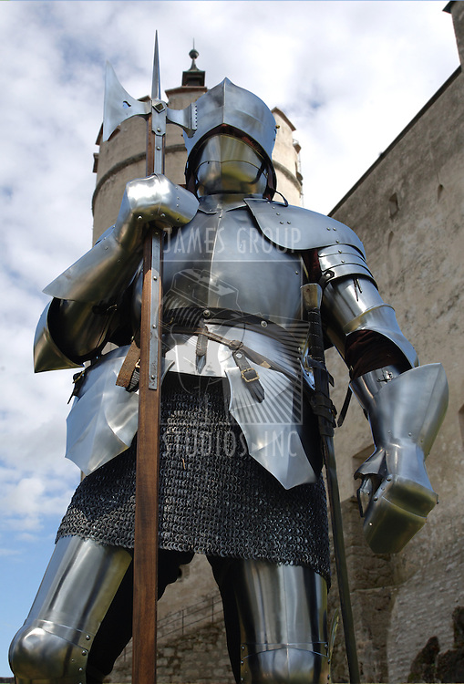 Worm's eye view of a knight standing in front of a mediaeval castle