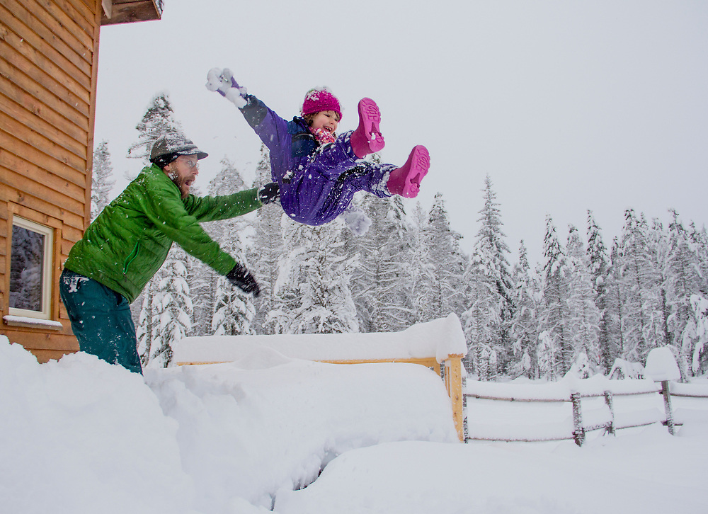 A father has fun with his daughter as he tosses her into a deep piles of snow on a cold winter day.