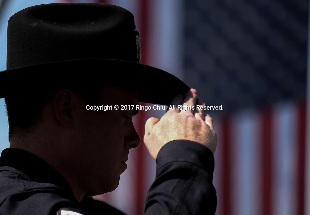 A police officer salutes as the hearse carrying the body of Whittier Police Officer Keith Boyer arrives at Rose Hills Memorial Park in Whittier, Calif., Friday, March 3, 2017. Boyer, who was fatally shot after responding to a traffic crash, was remembered today by thousands of law enforcement officers, friends and family as a dedicated public servant, talented drummer, loving friend and even a ``goofy'' dad.(Photo by Ringo Chiu/PHOTOFORMULA.com)<br /> <br /> Usage Notes: This content is intended for editorial use only. For other uses, additional clearances may be required.