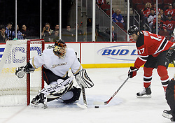 February 8, 2008; Newark, NJ, USA;  Anaheim Ducks goalie Jonas Hiller (1) makes a save on New Jersey Devils center Michael Rupp (17) during the second period at the Prudential Center in Newark, NJ. Mandatory Credit: Ed Mulholland-US PRESSWIRE