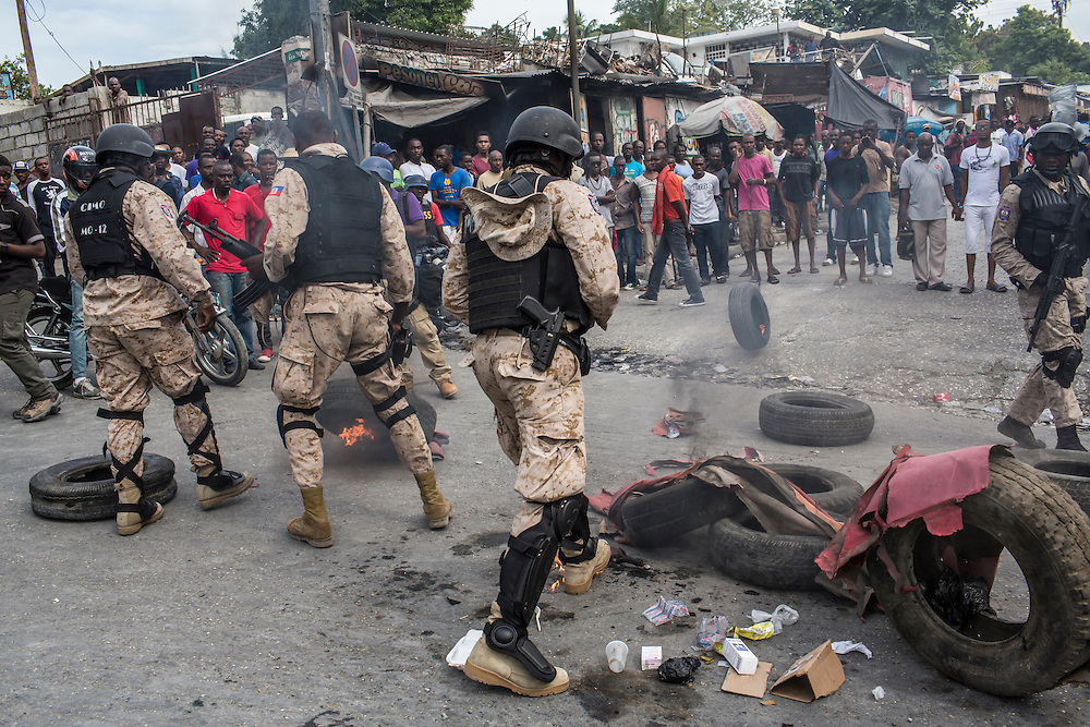 Police break apart a pile of burning tires and debris during an anti-government protest on Tuesday, December 16, 2014 in Port-au-Prince, Haiti. President Michel Martelly was elected in 2010 with great hope for reforms, but in the wake of slow recovery and parliamentary elections that are three years overdue, his popularity has suffered tremendously, forcing Prime Minister Laurent Lamothe to resign.