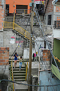 "2015/11/23 - Medellín, Colombia: Two girls walk down the stairs of barrio Pablo Escobar in Medellín. Originally called ""Medellin Sin Tugurios,"" or Medellin Without Shanty Towns, Barrio Pablo Escobar is located high up on the eastern slope of Medellin, where Pablo Escobar built 400 houses, which he gave to poor people that used to live in a mountain of garbage in the Moravia barrio. (Eduardo Leal)"