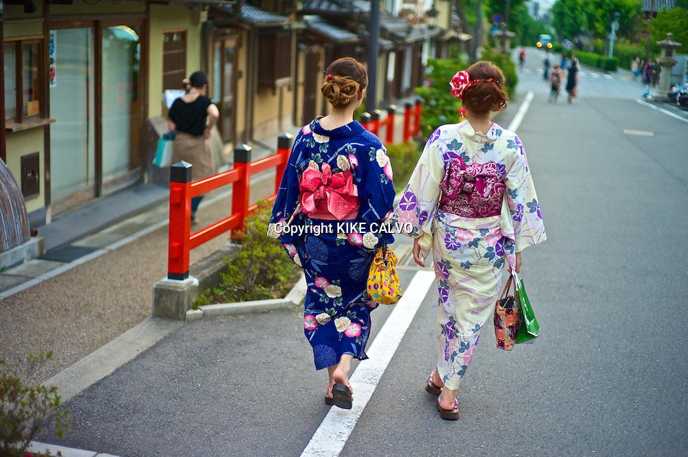 Asian women in traditional kimonos exploring the stores and shops near the Kiyomizu Temple.