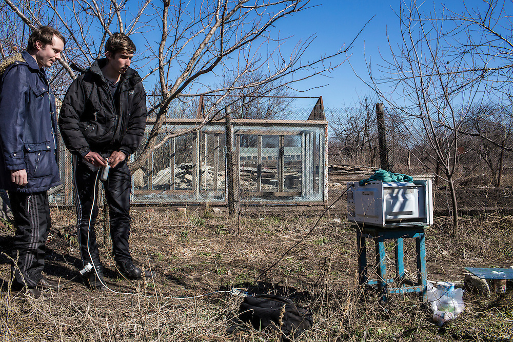 LUHANSK, UKRAINE - MARCH 16, 2015: Aleksandr Kryukov, left, and Pavel Pavlov conduct a scientific experiement involving microwaves in the yard of the house where Kryukov lives with his grandmother in Luhansk, Ukraine. The two have created a series of popular YouTube videos involving scientific experiements. CREDIT: Brendan Hoffman for The New York Times