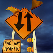 Texas Department of Transportation highway sign, Two Way Traffic, with two orange flags and two yellow warning flashing lights. Two way traffic sign was shot in the Texas Hill Country near Brenham. Dark clouds in the sky behind sign. Road constuction, slow down, road work.