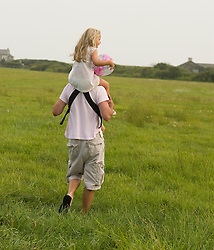 Father carrying his 6 year old daughter on his shoulders through a grassy field in East Hampton, New York