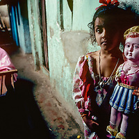 Girl living in a brothel in Mumbai India with her doll.