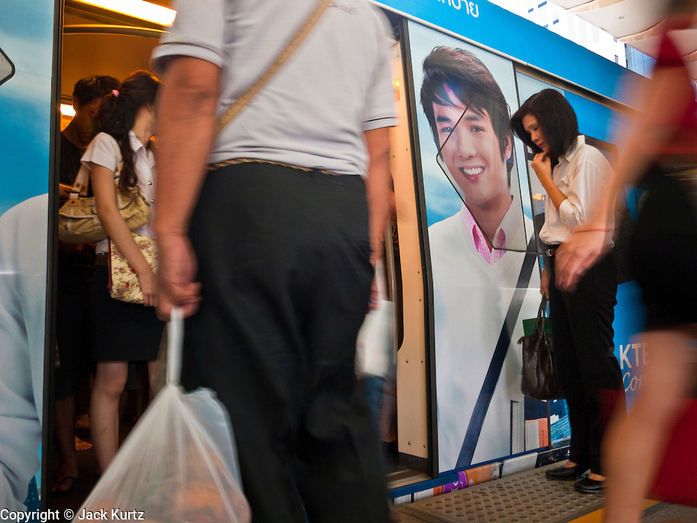 14 JULY 2011 - BANGKOK, THAILAND:   People board the BTS Skytrain in the Nana Station on the Sulhumvit line in Bangkok. The Bangkok Mass Transit System, commonly known as the BTS Skytrain, is an elevated rapid transit system in Bangkok, Thailand. It is operated by Bangkok Mass Transit System Public Company Limited (BTSC) under a concession granted by the Bangkok Metropolitan Administration (BMA). The system consists of twenty-three stations along two lines: the Sukhumvit line running northwards and eastwards, terminating at Mo Chit and On Nut respectively, and the Silom line which plies Silom and Sathon Roads, the Central Business District of Bangkok, terminating at the National Stadium and Wongwian Yai. The lines interchange at Siam Station and have a combined route distance of 55 km.    PHOTO BY JACK KURTZ