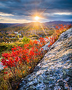 Red blueberry bushes light up as the sun finds a hole in the clouds and peeks through on Mount Battie in Camden Hills State Park. This scenic view includes dark autumn storm clouds, Maine's famous granite on the rocky hillside, and a small bend in the road in the town below.
