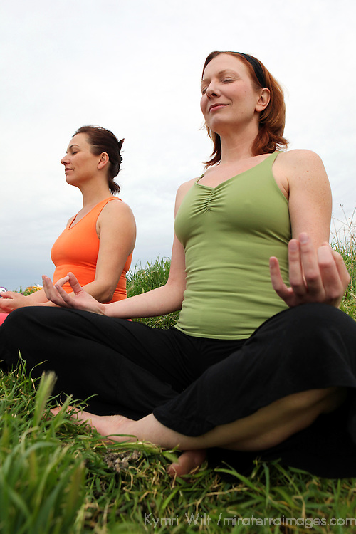 USA, California. Two mature healthy women share outdoor meditation.