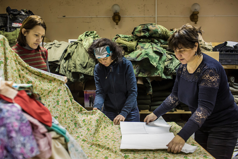 DNIPROPETROVSK, UKRAINE - NOVEMBER 16, 2014:  Yana Sobolenko, 39, an engineer, left, Lyudmyla Makaida, 48, a designer, center, and Tanya Volynets, 46, a lawyer, right, arrange a pattern they will use to cut fabric to make underwear for soldiers at the Dnipropetrovsk Volunteer Logistics Center, a charity organization that produces supplies for pro-Ukrainian fighters battling rebels in the country's East, in Dnipropetrovsk, Ukraine. CREDIT: Brendan Hoffman for The New York Times