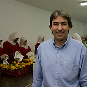 Helmy Abouleish, (c) Managing Director of the leading Egyptian Organic foods and products producer, Sekem Group, poses for a portrait as Egyptian women prepare fresh peppers for export at the Sekem farm Nov 4, 2008 in Belbeis, Egypt. Helmy's father, Dr. Ibrahim Abouleish founded the project in 1977 on what was then barren desert, and since has grown it into a lush oasis ecompassing several farms, production plants, schools and even a local medical facility.