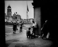 Shoeshine and a newspaper on the Zocalo in front of the Catedral Metropolitano begun in the 16th century and built atop the massive Aztec temple complex demolished by the Spaniards.  Mexico City, Mexico.