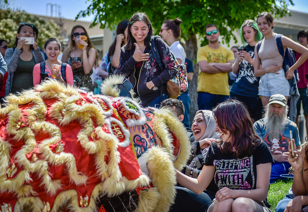 rer041317a/metro/04.13.2017/Roberto E. Rosales <br /> UNM students were treated to international delights as the campus celebrated the International Festival.  Pictured in the bottom middle is Leena Aggad(Cq)a UNM student from Palestine laughing as a member of the Lion Dance team approaches her with the head of a dragon during a performance dance. <br />  Albuquerque, New Mexico(Roberto E. Rosales/Albuquerque Journal)