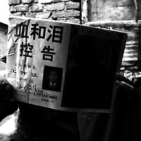 """BEIJING, DECEMBER-26:  a woman holds a leaflet titled """" Blood and tears """" that relates a family members unfair treatment .. In the past decades, hundreds of thousands of Chinese from the provinces have descended upon Beijing in hopes of attracting attention from higher authorities regarding their civil law cases. These cases vary from work accidents, violence against family members, murder, extortion, and the majority of which stem from a corrupt rural legal system...The tradition of petitioning to higher authorities in the Chinese capital reaches back to Imperial times. Outside the city center of Beijing, petitioners' villages sprung up as those seeking justice face long delays in being heard. The petitioners today face tremendous obstacles in having their cases heard; authorities are overworked due to the sheer number of complaints, which are often clumsily presented without aid of a legal adviser. In addition, Provincial as well as undercover police try to stop the petitioners from going to the National Petition offices to file their cases. If caught, they are briefly sent to an unofficial detention centre where they are held and forced to take the train back to the provinces. For many of the petitioners, it has become their life mission to make the regular journey to the capital only to be sent back without ever having been heard...The number of petitioner villages has been reduced significantly as the preparations for the 2008 Olympics progress. Many fear these villages will be gone by the summer of 2008.."""