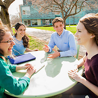 Students having a discussion at an outdoor table on the Brandeis University campus in Waltham, MA.