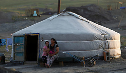 A picture made available on 05 July 2012 of a Mongolian woman and her daughter sitting outside their ger in a mining site in the mining town of Nalaikh in Mongolia, 02 July 2012. Once a thriving mining town, Nalaikh is one of first and oldest mining site in Mongolia but has seen a decline in its fortune as mining disasters and accidents plague the site. With little government oversight, only a handful of small companies and informal miners work on the site with scant regard to safety standards. Mongolia is rich in a variety of natural resources including forests, coal, iron ore, gold and copper. Expansion of the mining industry has turned the sector into the most important income source and led to an economic growth rate last year of around 17 per cent. The majority of raw materials are exported to China. Seeking to to reduce the dependency on China for exports and Russian imports, Mongolia has embarked on a policy of closer economic ties with other countries such as Germany, Canada and the United States. Despite impressive growth rates, about one-third of the population lives below the poverty line while unemployment and inflation are high.